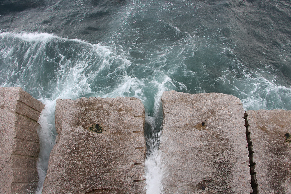 Ocean waves crashing against large concrete steps, viewed from above. Taken in Victoria.
