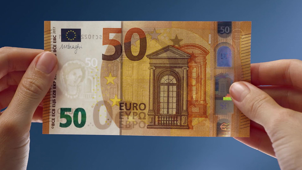 Person holding a €50 note in both hands