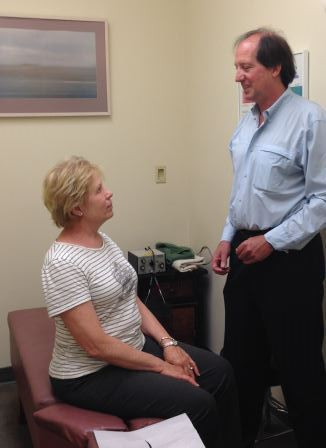 Chiropractor Dr. Dan Smith advises a patient in his San Rafael office.