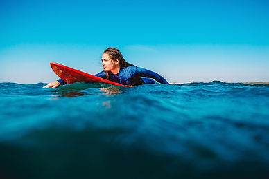 Surf girl floats on surfboard. Woman in