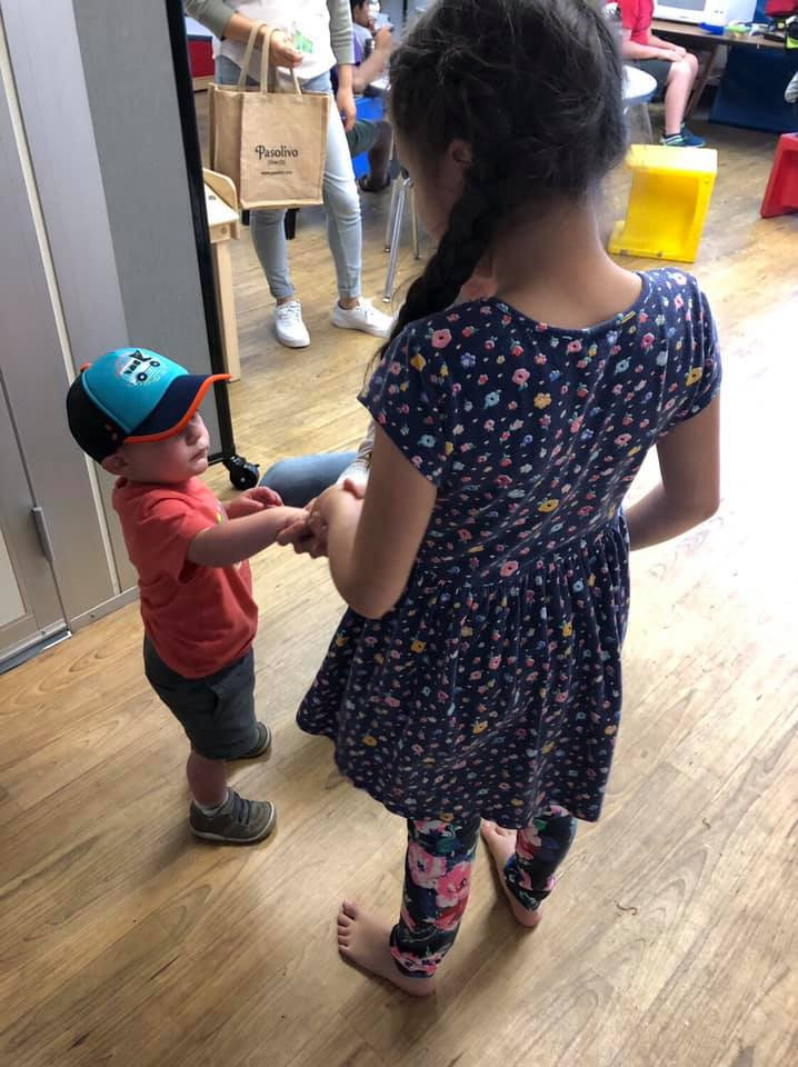 A young girl wearing a blue flowered dress and matching leggings holds hands with a toddler in a red t-shirt and blue had at Open Mind School