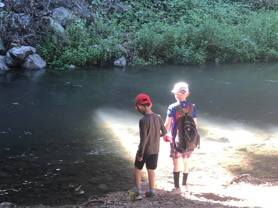 Two children, one in a grey shirt and black pants and one in a blue and red jersey with red pants, are standing by a river and holding hands on an Open Mind School field trip