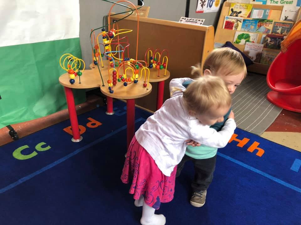 A toddler in a pink skirt and white shirt hugs a toddler in a teal shirt and grey pants. They are in an Open Mind School classroom with a blue rug under them and a colorful wooden bead maze behind them.