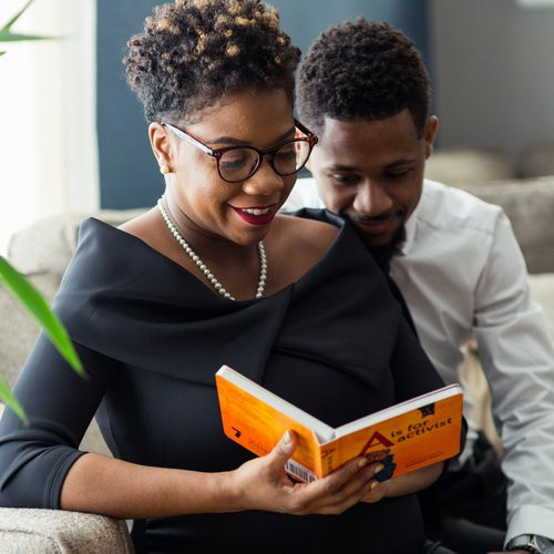 Beautiful black couple doing some reading together and enjoying it