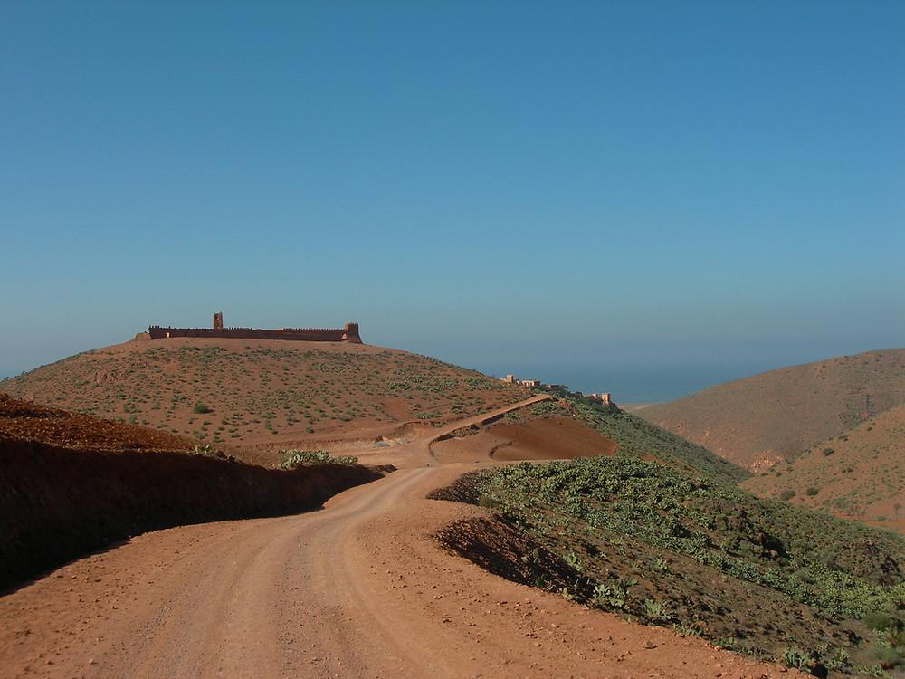 Sur la colline, le fort en ruines. A droite, le riad Les Trois chameaux