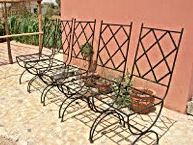 Des chaises en fer forgé et une table en zelliges avec des étoiles