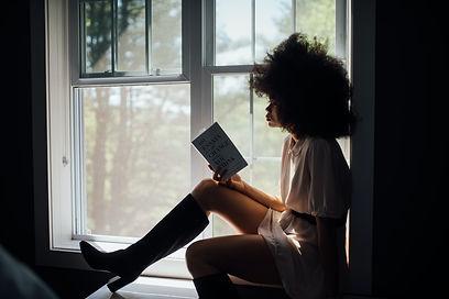 woman-sitting-on-window-reading-book-222
