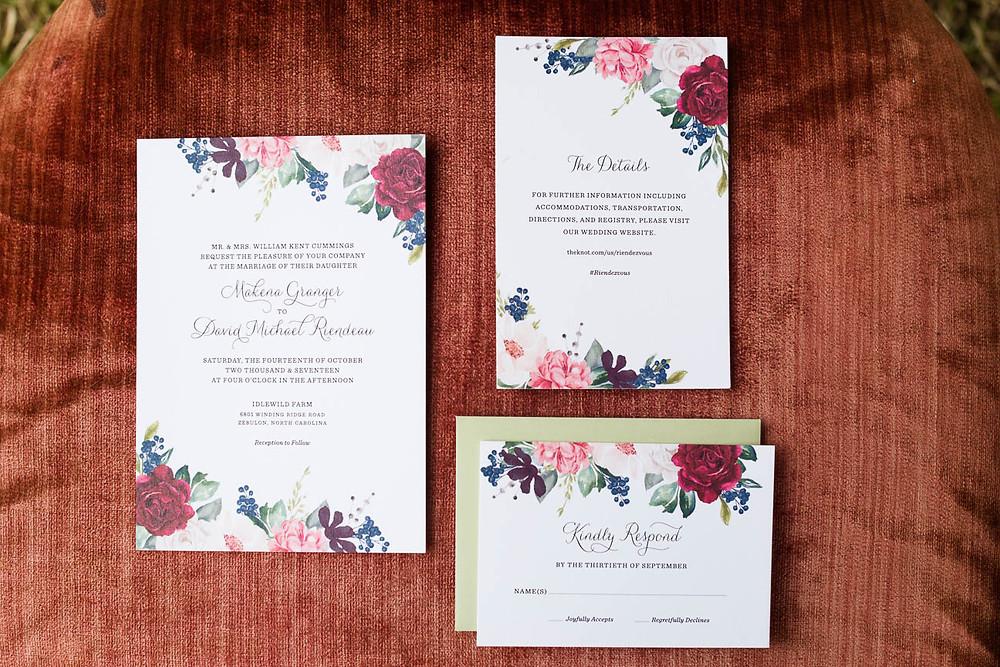 floral wedding invitation suite on red velvet chair