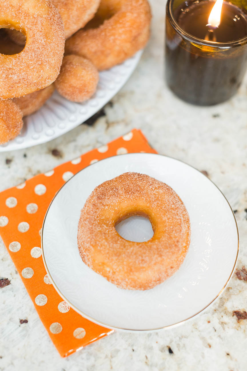 cinnamon donut on plate with orange dotted napkin and candle