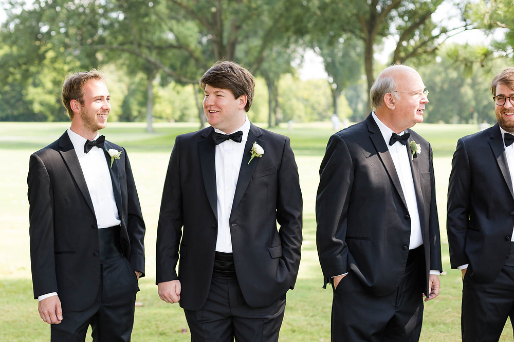 groom laughs with groomsmen before his wedding ceremony
