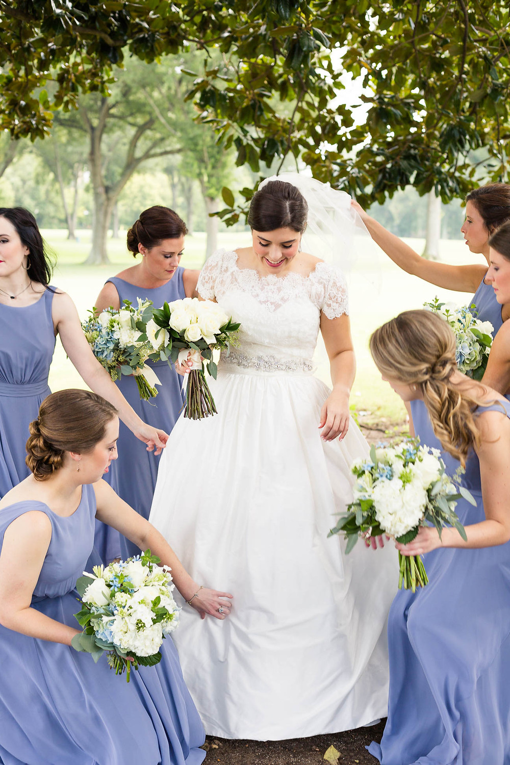 bridesmaids help bride get ready under a tree on a golf course