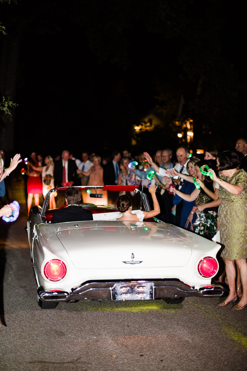 image of bride and groom driving away in vintage white Thunderbird convertible