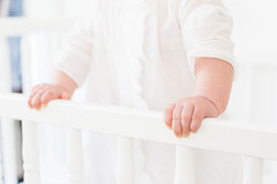 baby girl's hands on crib