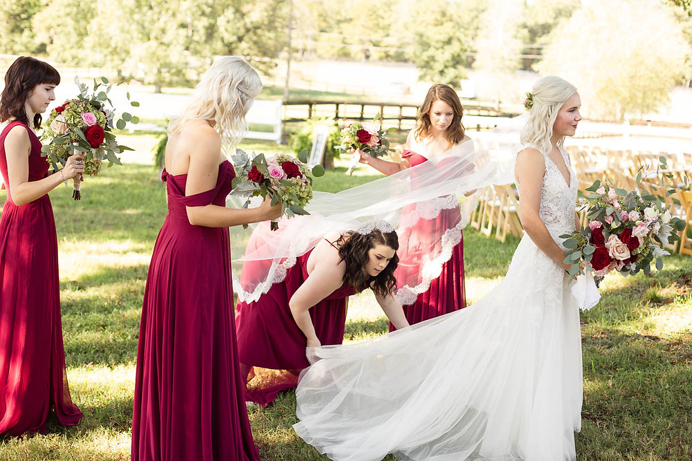 bridesmaids help the bride with her dress and veil