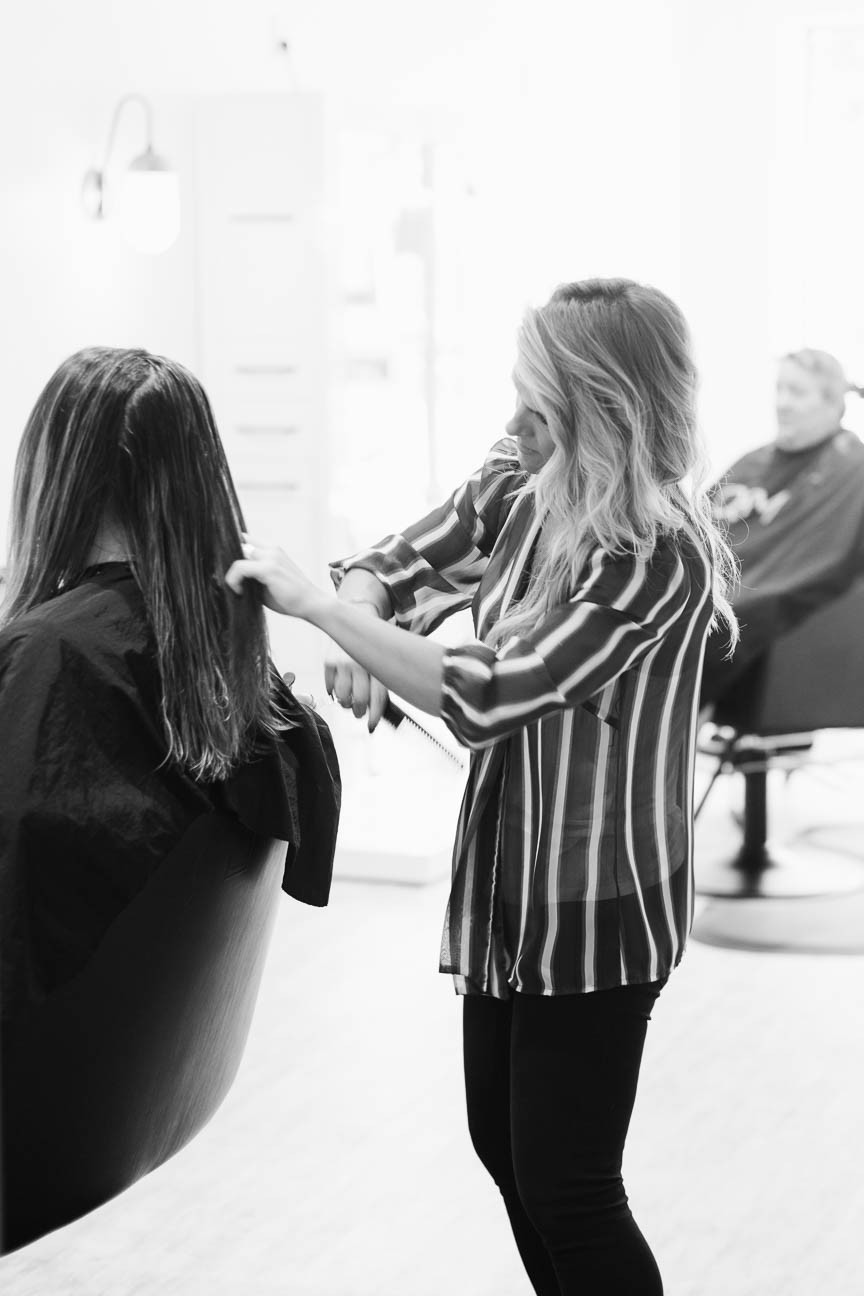 Jessica combs hair before cutting it in her luxury salon