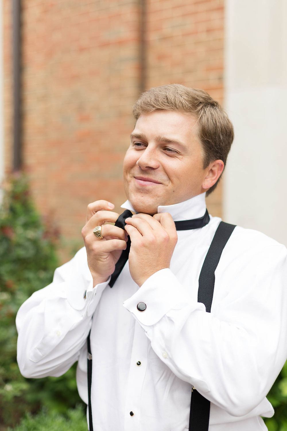 groom ties his bowtie on his wedding day