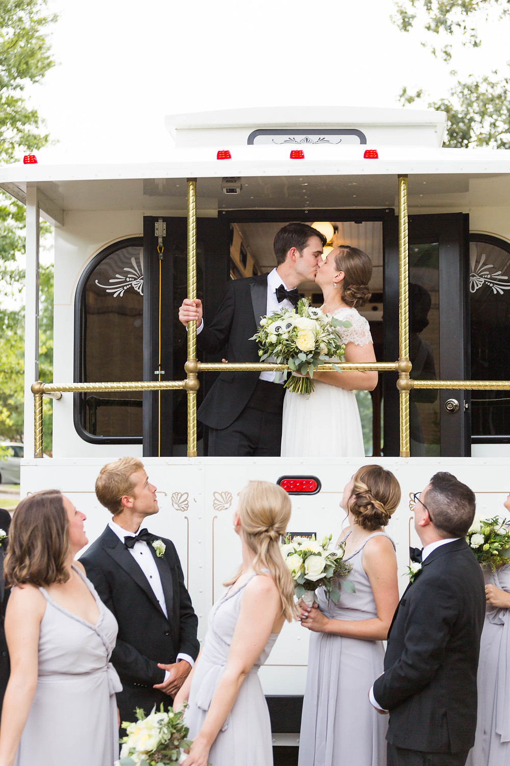 bride and groom kiss on trolley as wedding party looks on
