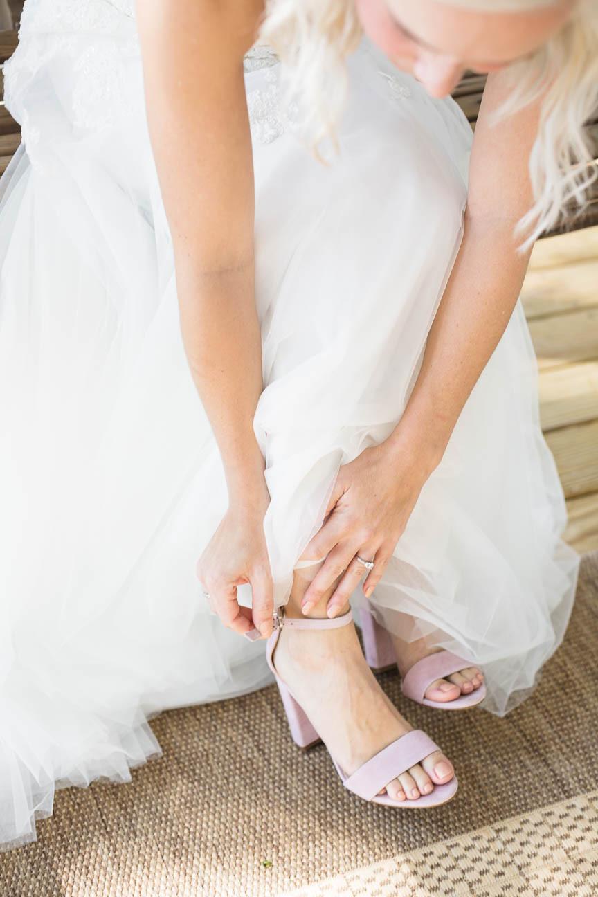 bride buckles her pink suede wedding shoes