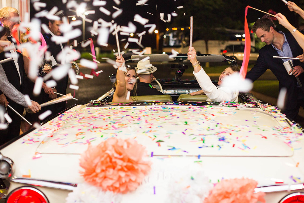 image of a couple throwing confetti out of a convertible after their wedding