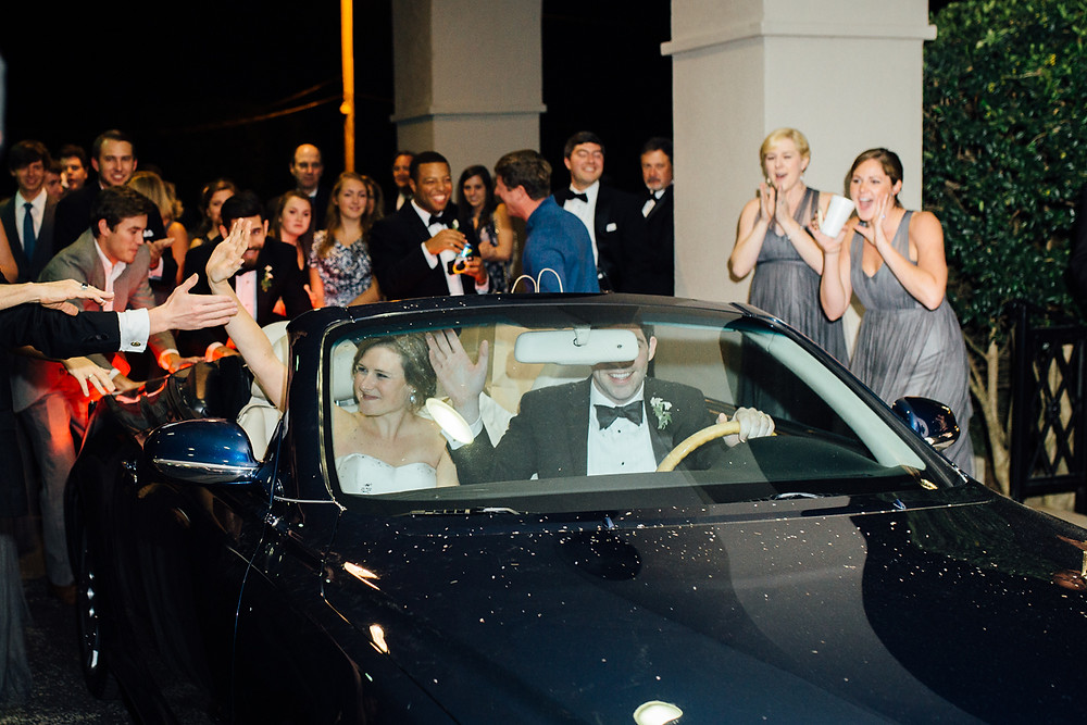 image of couple leaving wedding in a navy convertible