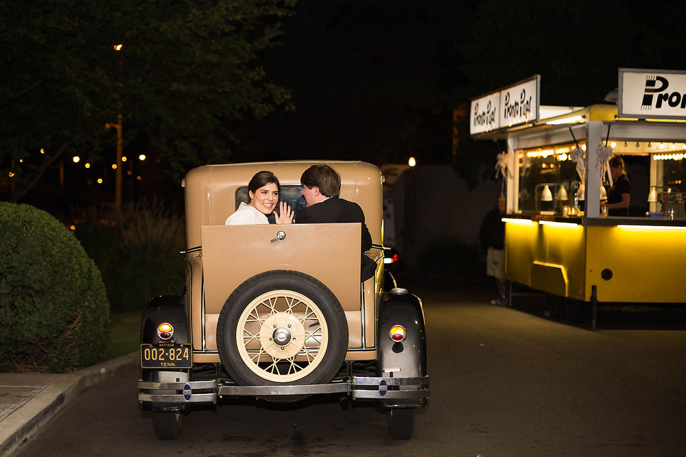 bride and groom leave wedding in vintage car