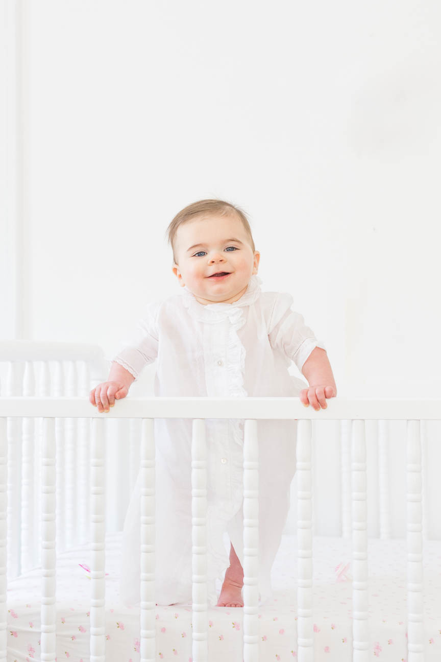 baby girl stands in crib