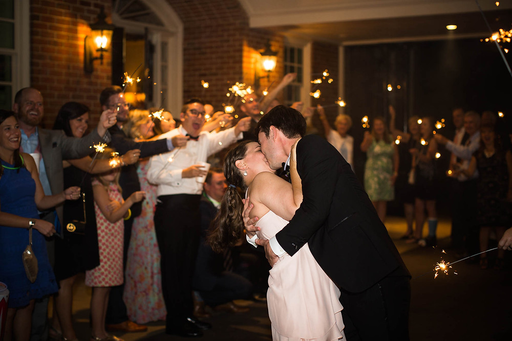 newlyweds kiss while guests cheer with sparklers