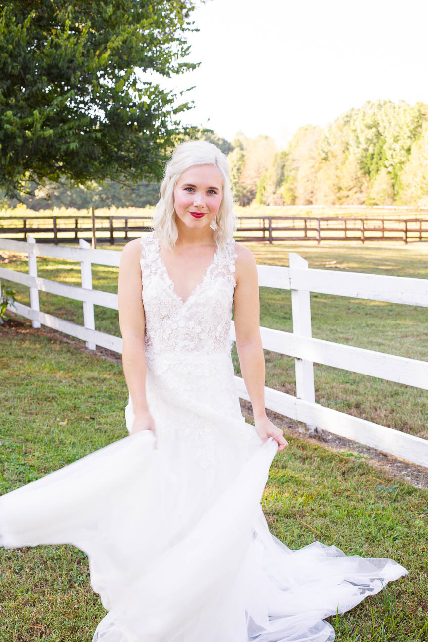 bride sways dress in front of her horse farm