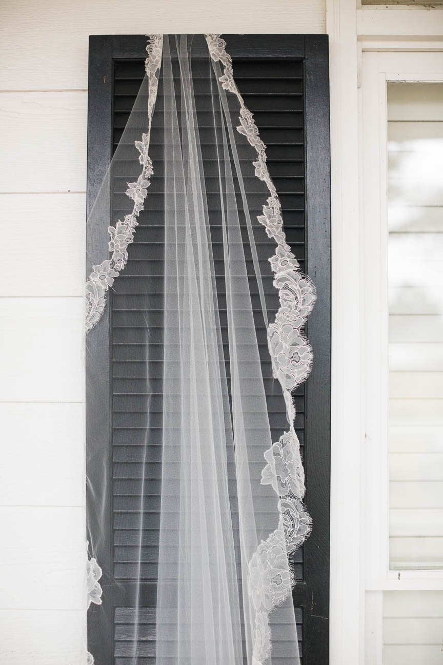 bride's lace trimmed veil hanging on a shutter outside of her parent's farmhouse in Raleigh