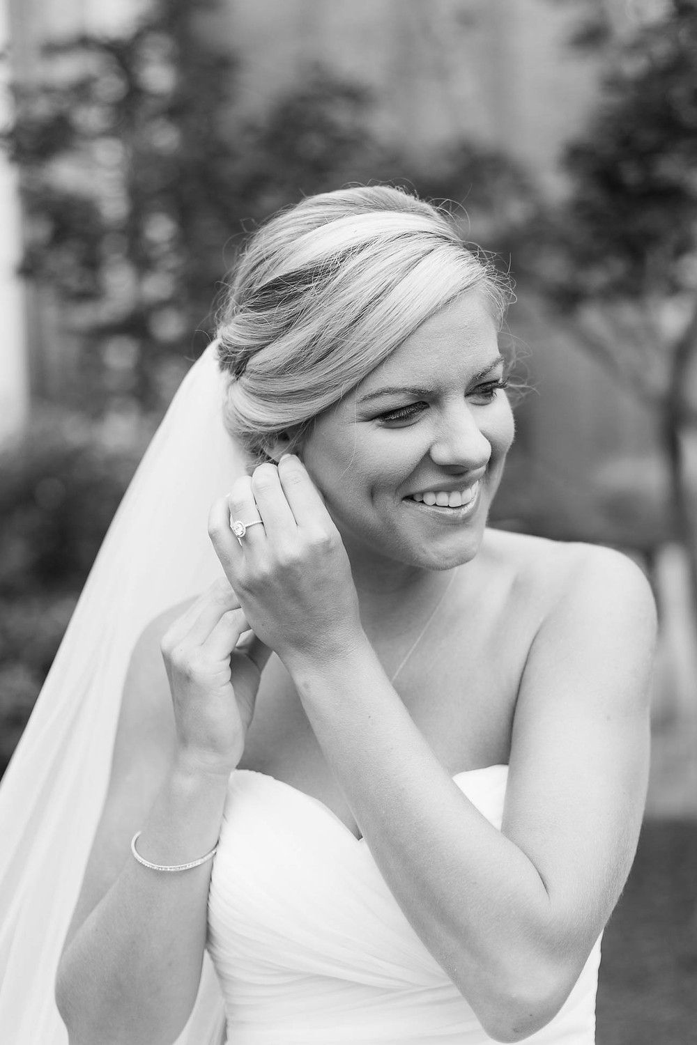 black and white portrait of bride putting her earrings in