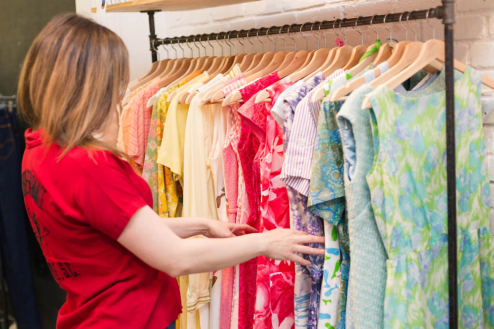 store owner flips through her inventory of vintage pretty vintage dresses
