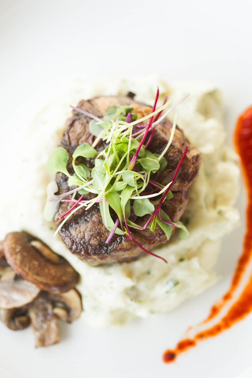image of steak on top of mashed potatoes with micro green garnish