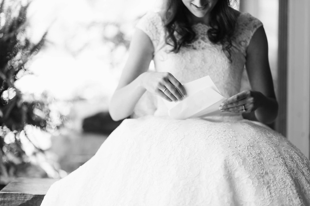 bride reads a note from her soon to be husband on their wedding day