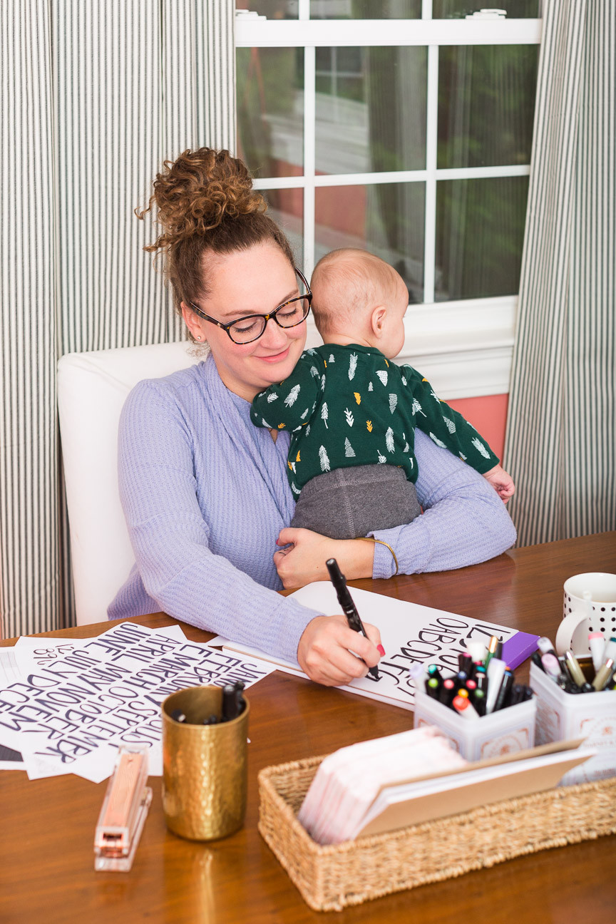 image of a graphic designer hand lettering and holding her baby