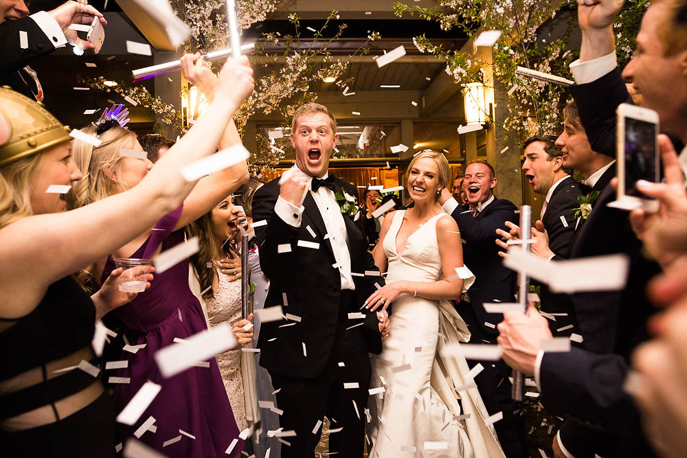 image of bride and groom departing to white paper confetti