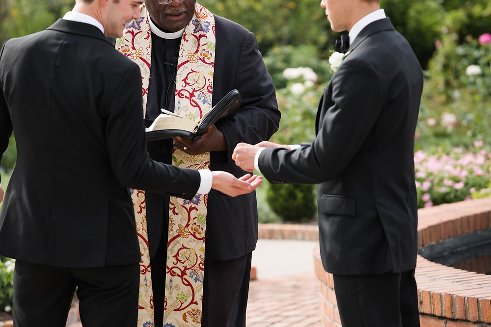 the best man gives the rings to the groom at a rose garden ceremony