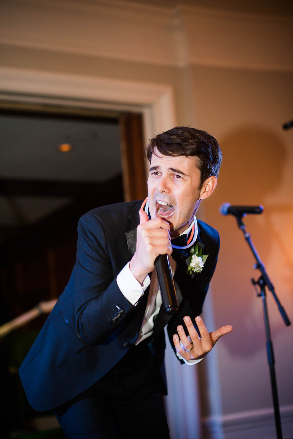 groom performs his favorite song on stage at his wedding reception