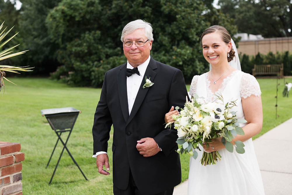 bride's father walks her down the aisle at her garden ceremony