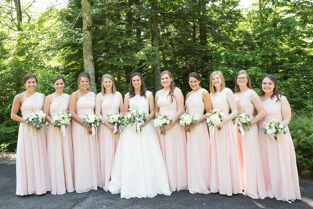 bride and bridesmaids stand in front of trees with flowers, pink bridesmaid dresses