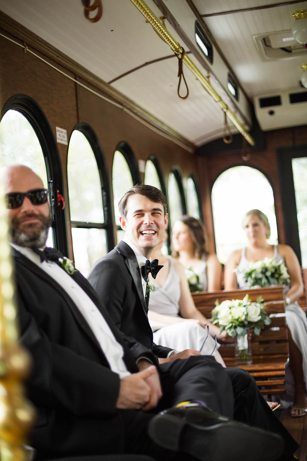 groom laughs as he rides a trolley to his wedding ceremony