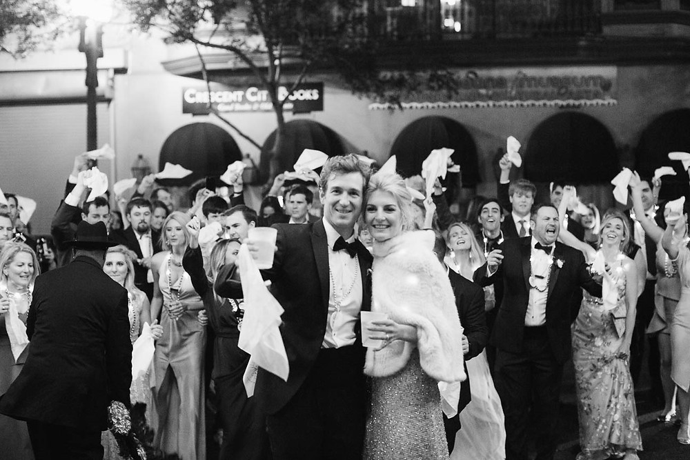 image of bride and groom stand with their guests outside of a New Orleans hotel