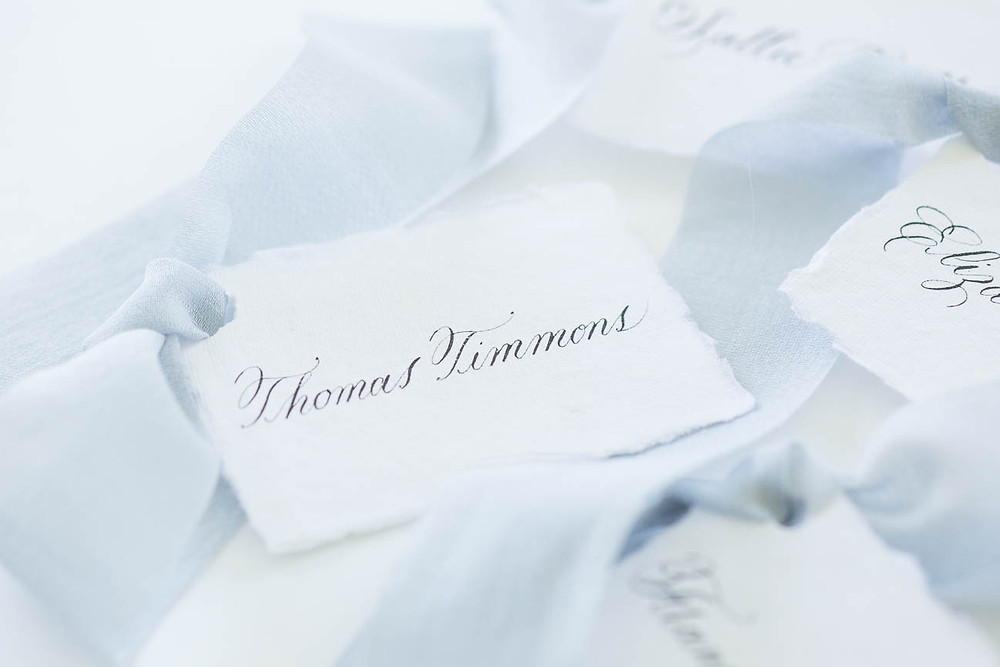 calligraphy place cards with blue ribbon