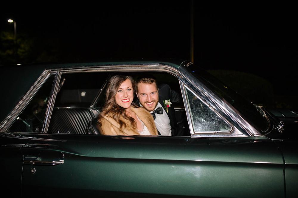 image of newlyweds sit in vintage Mustang before leaving their wedding