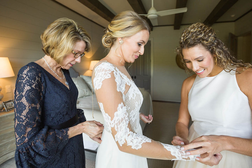 mother and sister help the bride get dressed for her wedding