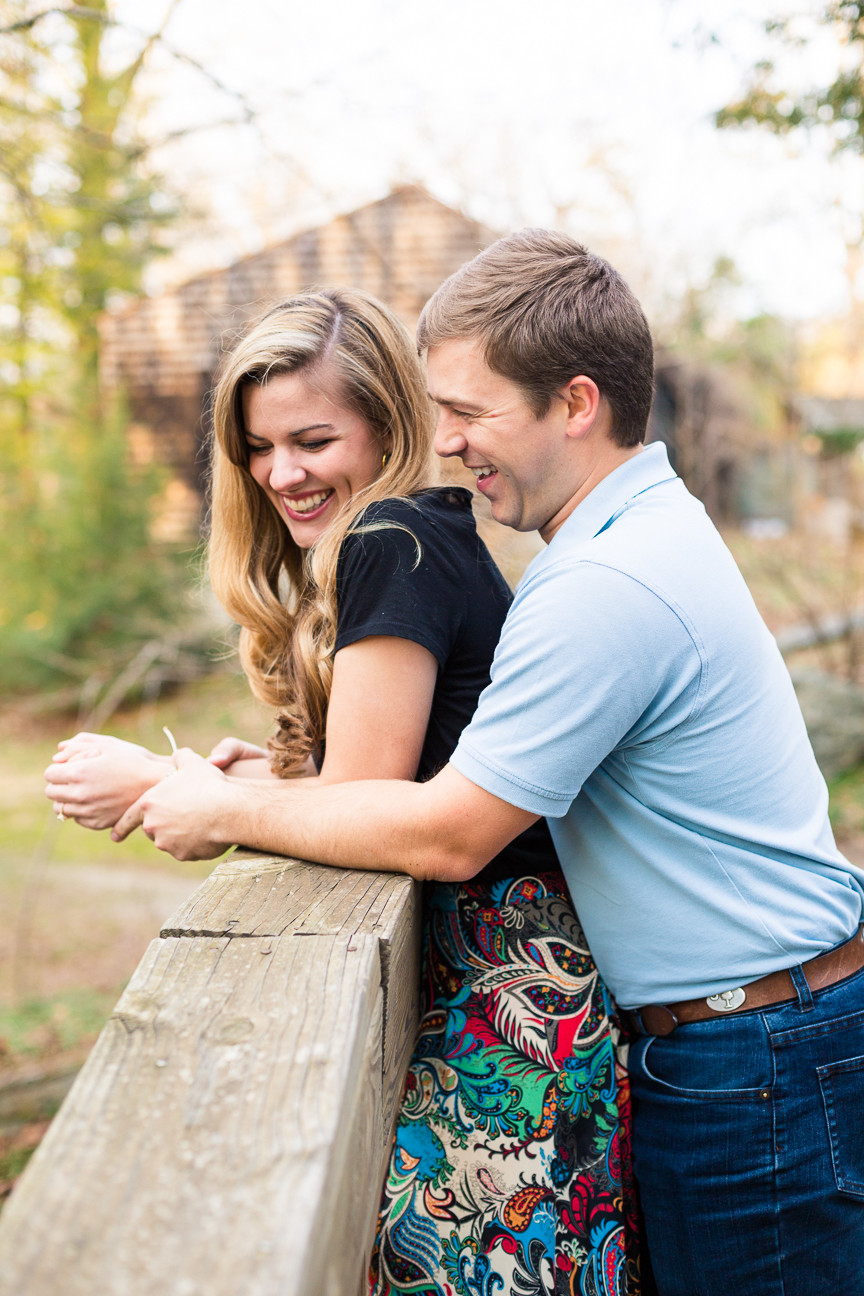 couple laughs together on a bridge, Asheville Engagement session