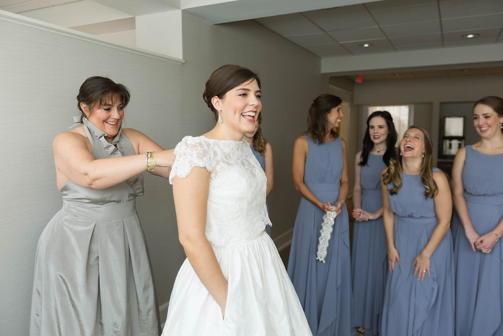 mother of the bride buttons her wedding dress as bridesmaids look on