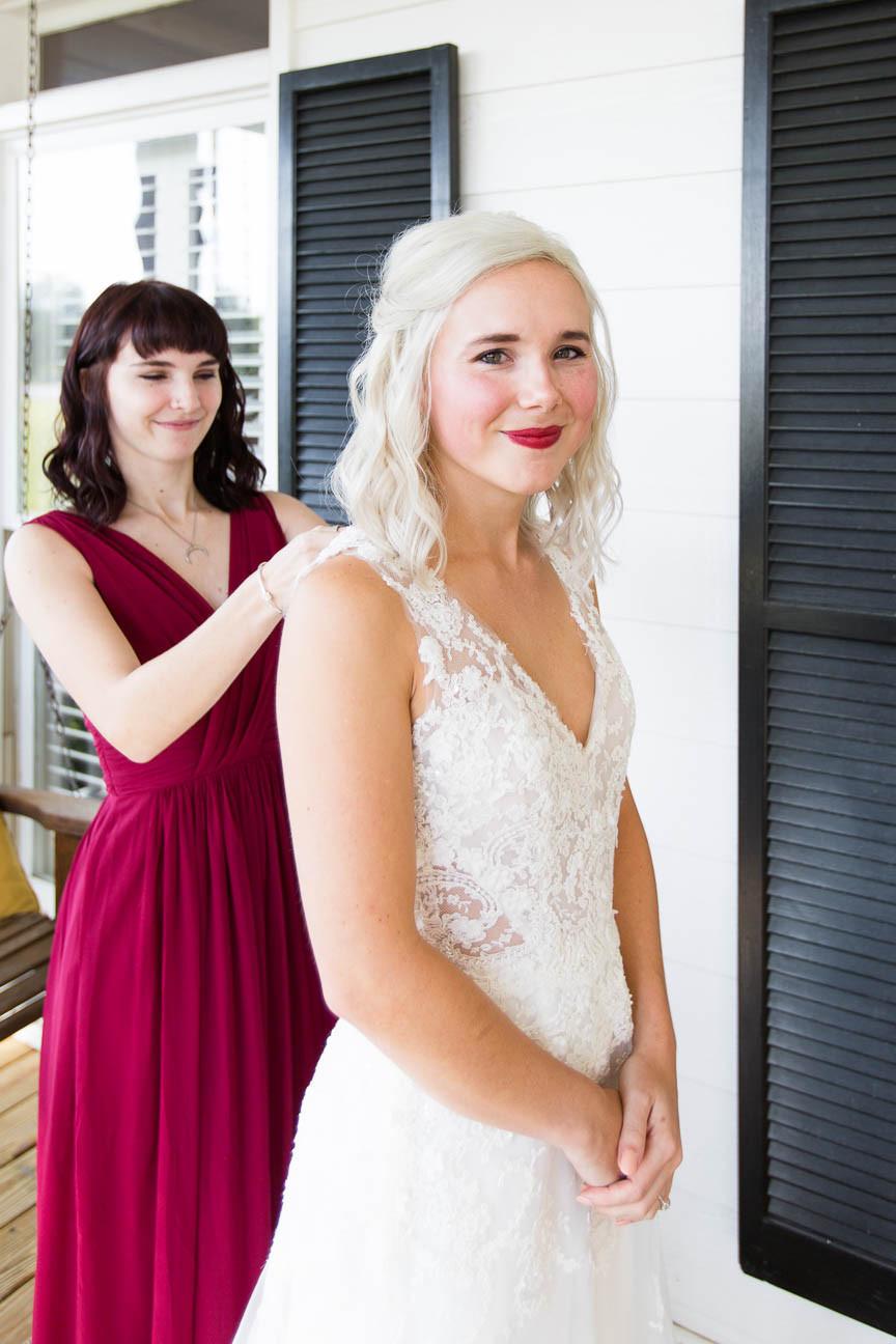 bride's sister helps zip the wedding dress