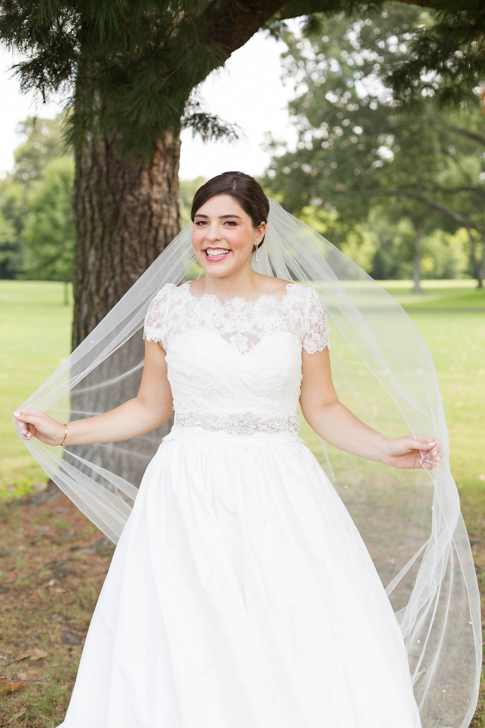 bride plays with veil on a golf course