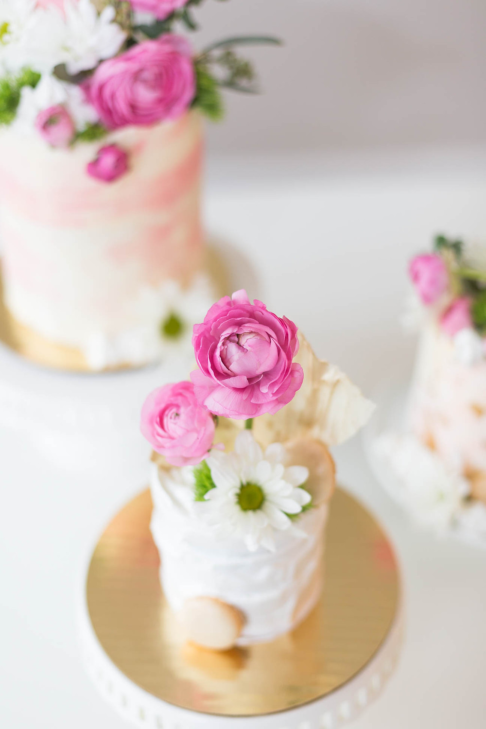 three mini wedding cakes decorated with pink ranunculus and with chocolate, cake decorating