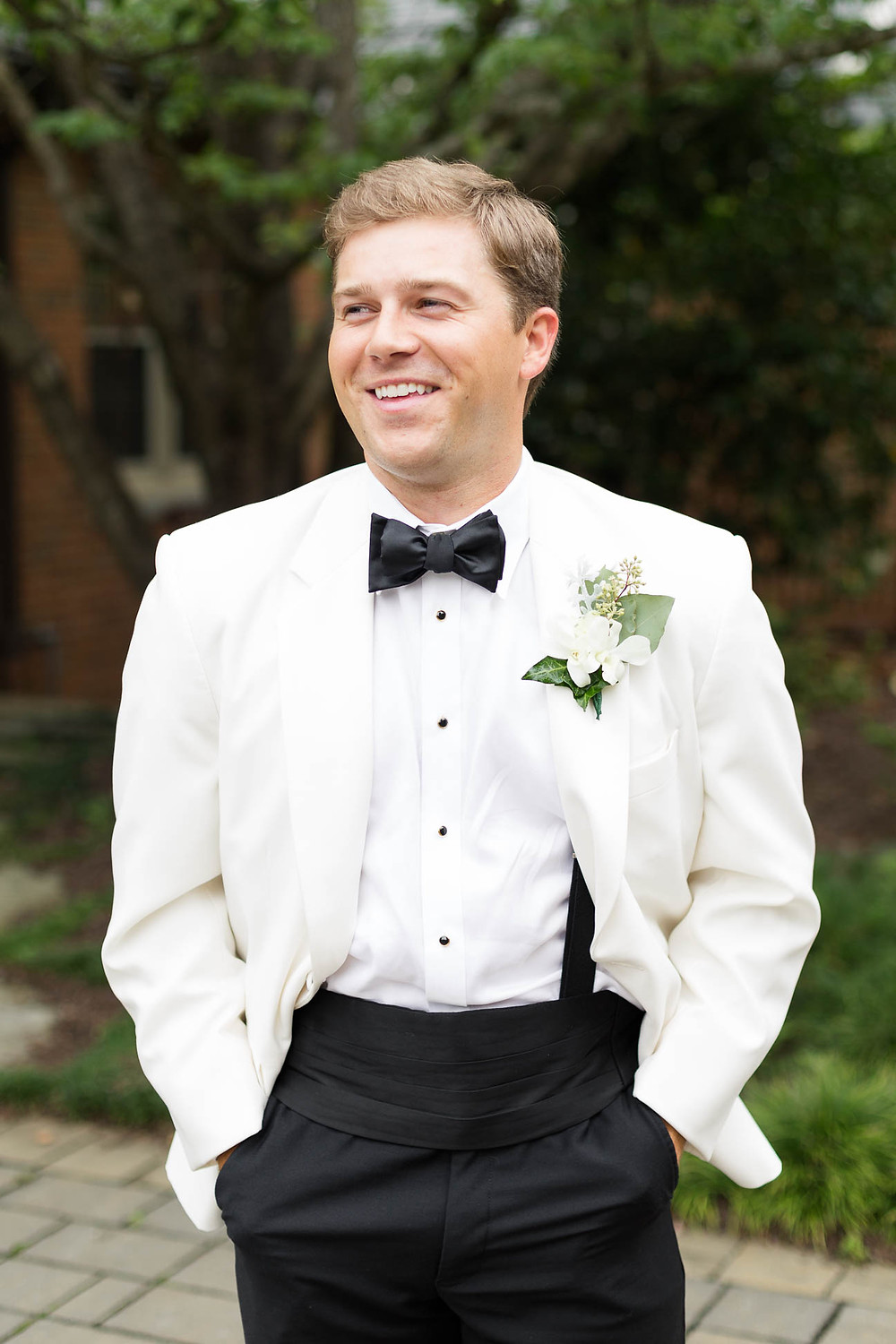 portrait of a smiling groom in his white jacket on wedding day